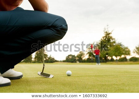 Woman golfer lining up for a putt Stock photo © dash