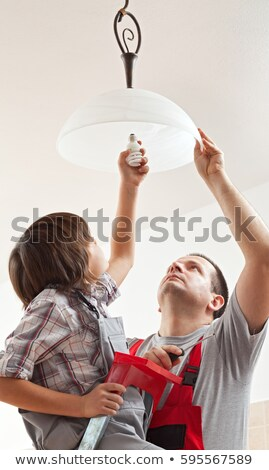 boy changing a lightbulb in ceiling lamp stock photo © lightkeeper