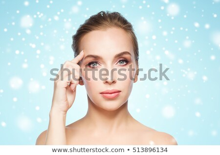 beautiful woman showing her forehead over snow Stock photo © dolgachov