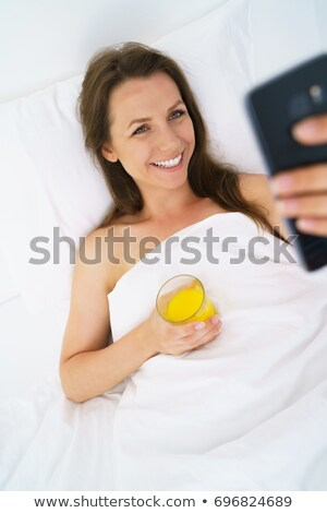 cute woman checks the smartphone and drinks orange juice in bed stock photo © vlad_star