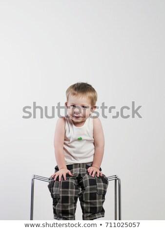 Shrugging boy sitting on stool Stock photo © IS2