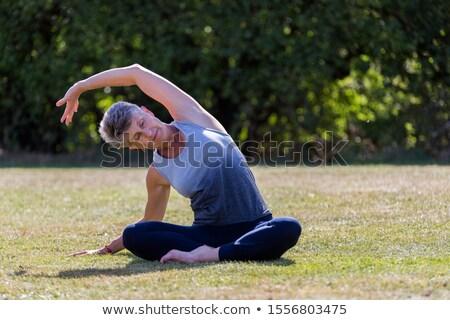 Idős nő jóga lábak nyújtás park Stock fotó © boggy