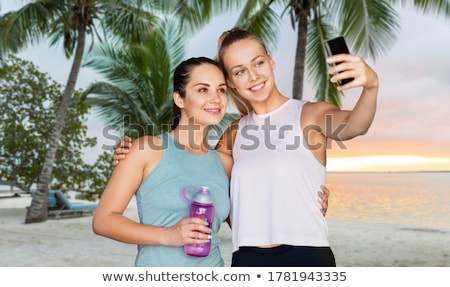 friends taking selfie by smartphone over bora bora stock photo © dolgachov