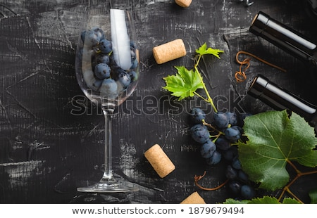 Elegant glass of red wine with dark grapes and corks inside vintage wooden box on black stone backgr Stock photo © DenisMArt