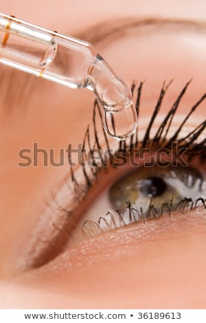 Closeup of eyedropper putting liquid into open eye Stock photo © galitskaya