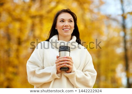woman with hot drink in tumbler at autumn park Stock photo © dolgachov