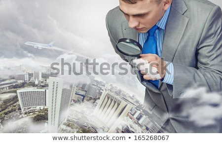 Curious man inspecting an object with a magnifying glass Stock photo © photography33