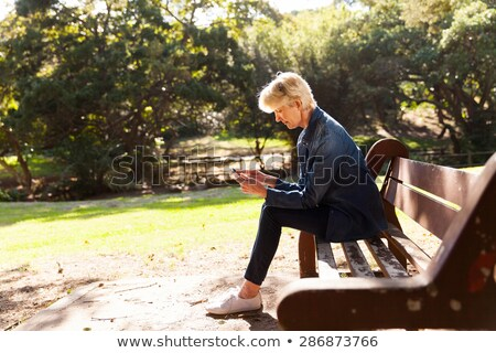 Attractive blonde girl using a smart phone. Stock photo © justinb