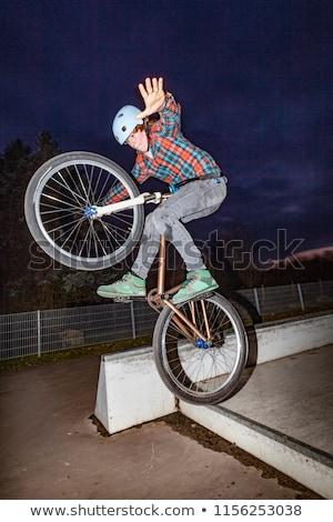Menino saltando bicicleta rampa noite céu Foto stock © meinzahn