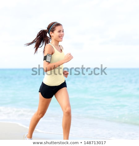 Woman jogging with earphones and smartphone. Stock photo © RAStudio