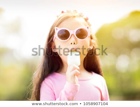 Young girl eating a popsicle in a park Stock photo © IS2