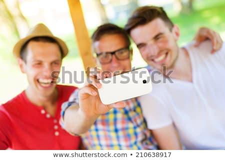 friends taking selfie with smartphone in beer garden stock photo © kzenon