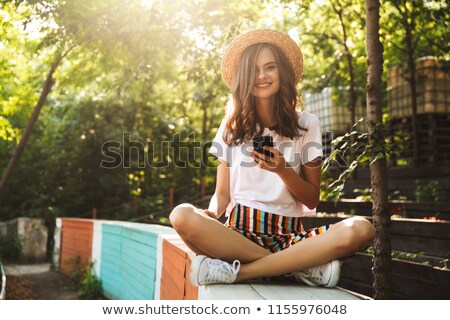 positve young girl using mobile phone at the park stock photo © deandrobot