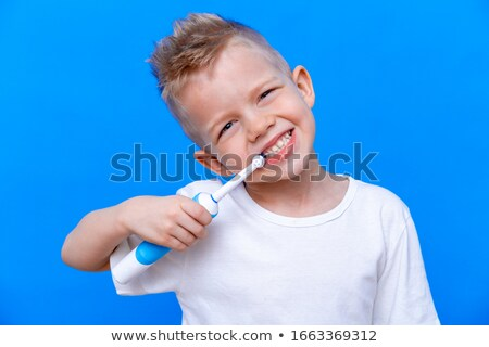 dentist with toothbrush and kid patient at clinic Stock photo © dolgachov