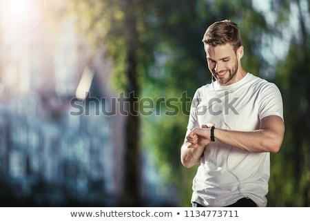 happy man looking at fitness tracker Stock photo © dolgachov
