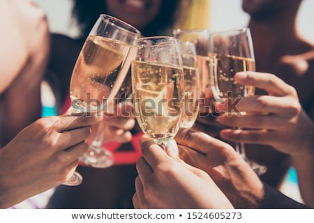 Clinking Glasses Of Champagne In Hands At Beach Stock photo © AndreyPopov