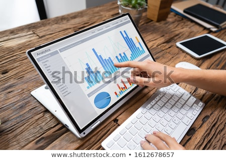 Businesswoman Analyzing Graph On Laptop At Workplace Stock photo © AndreyPopov