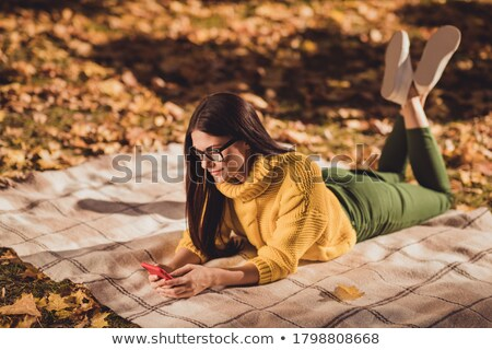 Woman texting with the phone on an autumn lawn in a park Stock photo © Kzenon