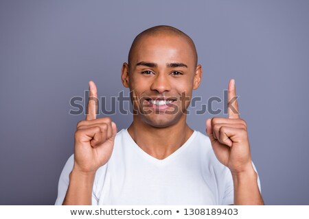 Close-up young masculine smiling, happy man in t-shirt, pointing left, gesturing and grinning proud, Stock photo © benzoix
