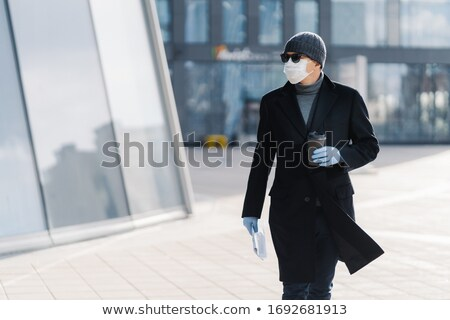 Horizontal shot of serious adult man carrying disposable cup of coffee, dressed in outerwear, protec Stock photo © vkstudio