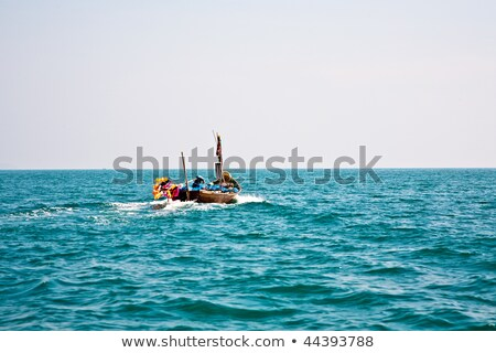 fisherman steers his small wooden boat out to the open sea stock photo © meinzahn
