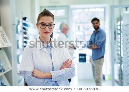 Female optician standing in front of eyesight test at hospital Stock photo © HASLOO