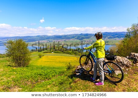 Woman cyclist standing near a bike on a mountain road Stock photo © vlad_star