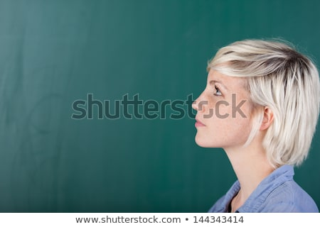 attractive young woman looking up to blank chalk board stock photo © feverpitch