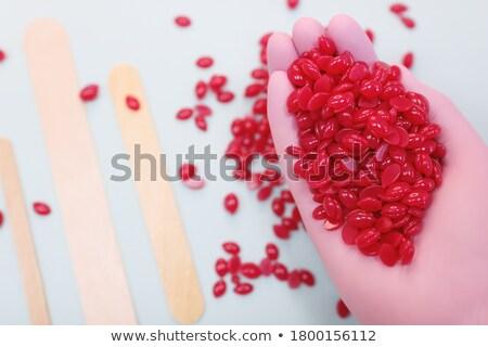 gloved hand holding small round pill Stock photo © Klinker