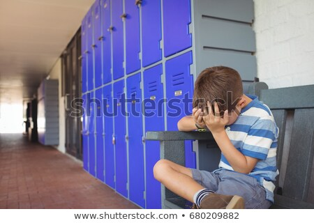 Sad boy sitting on pavement by lockers Stock photo © wavebreak_media