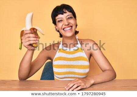 Portrait of a happy cheery girl eating bananas Stock photo © deandrobot