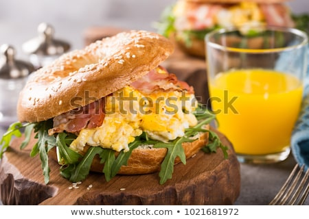 Bagels with scrambled eggs, rucola and fried bacon Stock photo © Melnyk