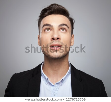 surprised businessman looks up to side while standing stock photo © feedough