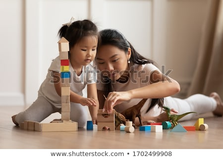 mother and child daughter building from toy blocks at home stock photo © lopolo