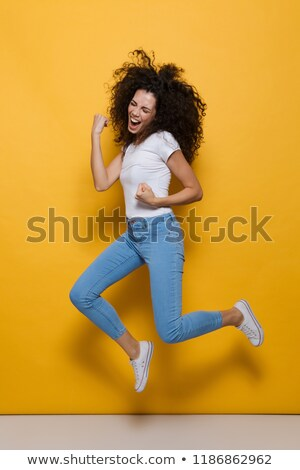 full length photo of positive woman 20s with curly hair having f stock photo © deandrobot