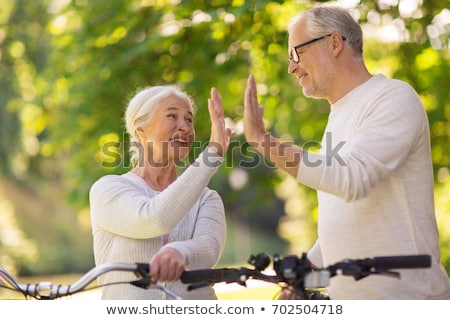couple with bicycles making high five in summer stock photo © dolgachov