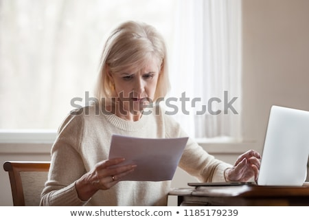 senior woman with money and bills at home Stock photo © dolgachov