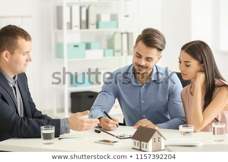 realtor with clipboard and customers at new office stock photo © dolgachov