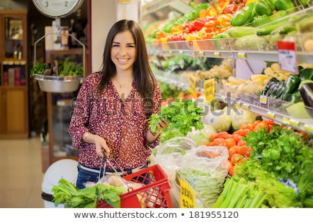 cute young woman buying vegetables at the market stock photo © boggy