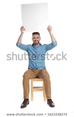 ülő boldog férfi tart óriásplakát felfelé Stock fotó © feedough
