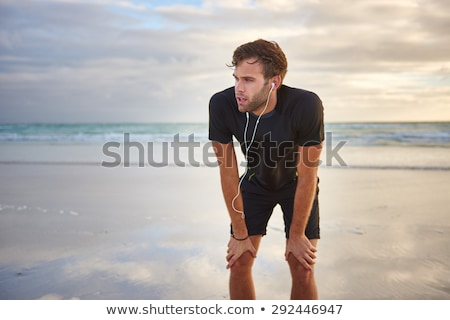 Tired young sports man standing on the beach have a rest. Stock photo © deandrobot
