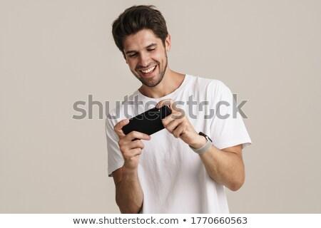 jóképű · izgatott · fiatal · szakállas · férfi · áll - stock fotó © deandrobot
