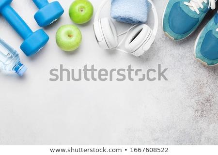 Fitness concept. Dumbbells, sneakers, headphones and apple Stock photo © karandaev