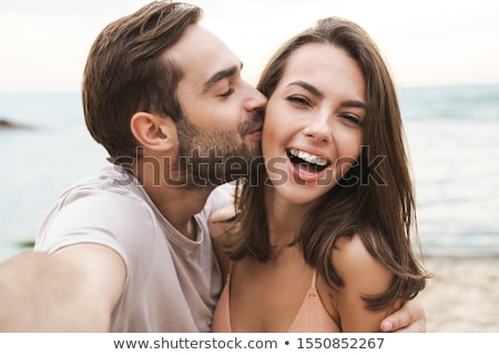 loving couple hugging outdoors on the beach stock photo © deandrobot