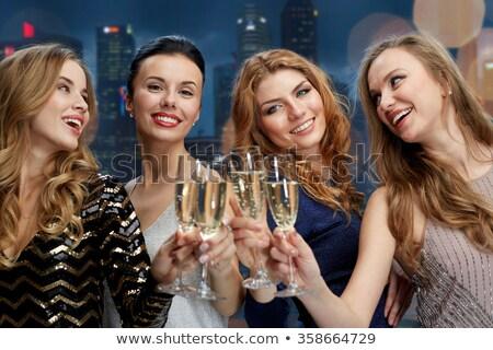 happy women clinking champagne glasses over black Stock photo © dolgachov