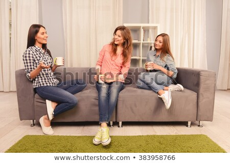Three sisters girls sit on the sofa at home Stock photo © Lopolo