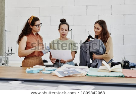 Pretty young female tailor and her colleague discussing new ideas Stock photo © pressmaster