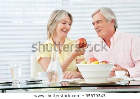 senior couple of woman and man eating apples fresh from the tree stock photo © kzenon