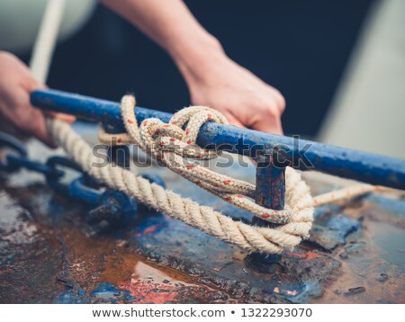A young woman is tying up her boat with a rope on the jetty Stock photo © boggy