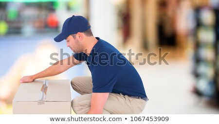Delivery man picking up box against blurry shopping centre Stock photo © wavebreak_media
